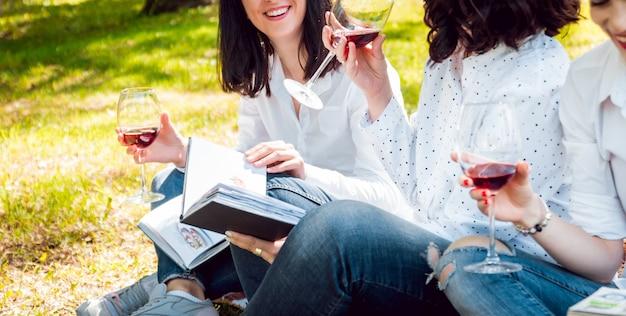 Jonge mooie meisjes met een glas rode wijn en boeken in het park.