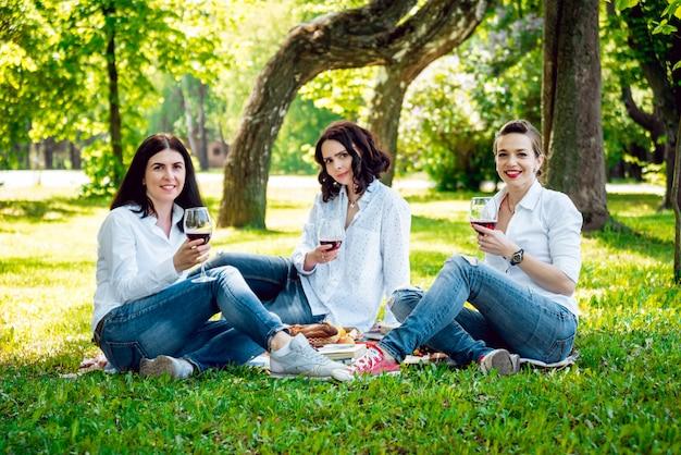 Jonge mooie meisjes met een glas rode wijn in het park