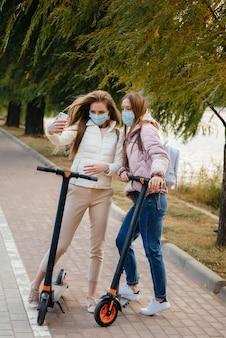 Jonge mooie meisjes met maskers rijden op een warme herfstdag in het park op een elektrische scooter en nemen selfies. wandeling in het park.