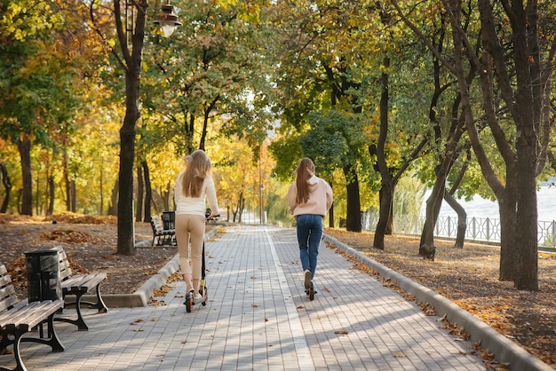 Jonge mooie meisjes rijden in het park op een elektrische scooter op een warme herfstdag. wandeling in het park.