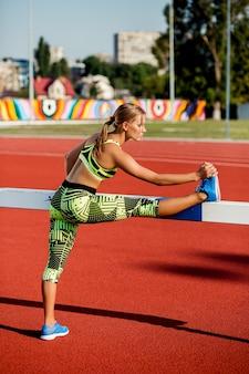 Jonge, mooie meisjesatleet in sportkleding die warming-up doet in het stadion