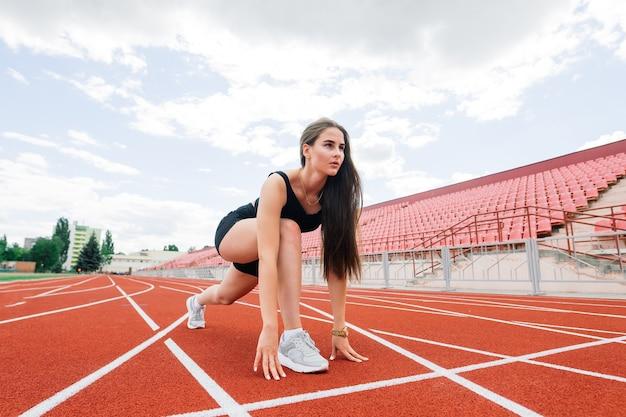 Jonge, mooie meisjesatleet in sportkleding traint en loopt, die zich uitstrekt in het stadion