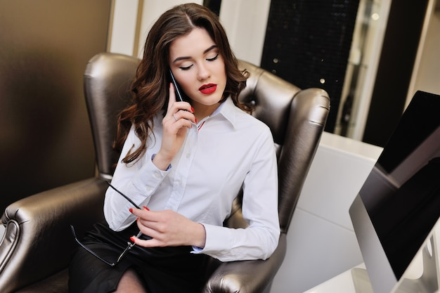 Jonge mooie meisjesbeambte of secretaresse in glazen die op de telefoon spreken