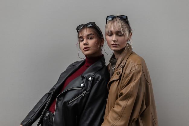 Jonge, mooie meisjesmodellen van zussen in modieuze leren jassen met een gebreide vintage trui staan buiten bij een grijze muur