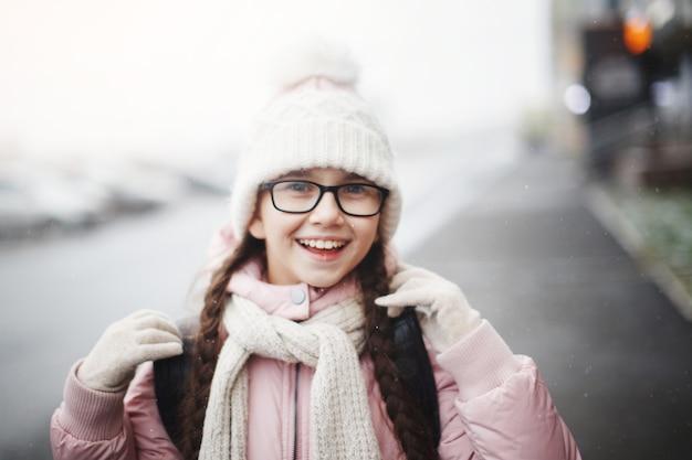 Jonge mooie meisjestiener met lang haar in een bril en in een modieuze witte gebreide muts lacht gelukkig en geniet van het leven buiten in de winter. detailopname.
