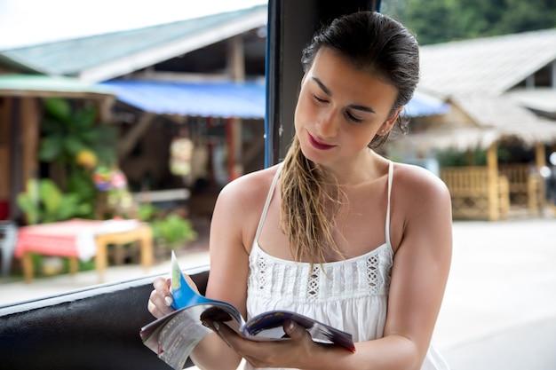 Jonge mooie meisjestoerist in een thaise tuk-tuktaxi, gezien het boek - kaart, concept van reizen