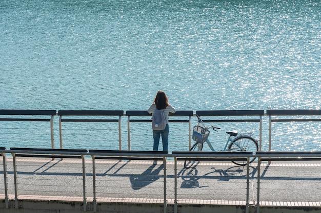 Jonge mooie meisjestribune dichtbij een fiets aan het bekijken het uitzicht op fietspad bij het meer in de ochtend. actieve mensen. buitenshuis