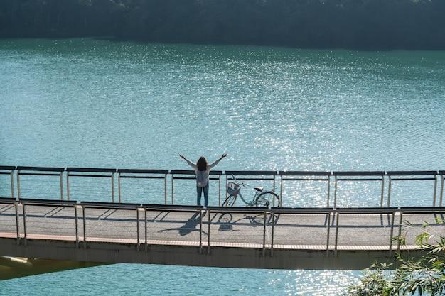 Jonge mooie meisjestribune dichtbij een fiets terwijl rust haar handen op fietssleep bij het meer in de ochtend. actieve mensen. buitenshuis