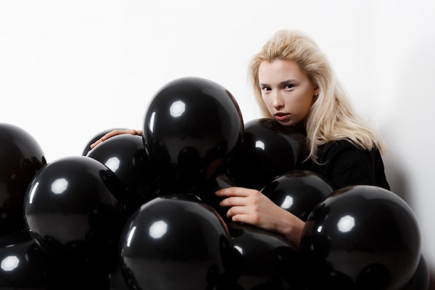 Jonge mooie meisjeszitting in zwarte baloons over witte muur.