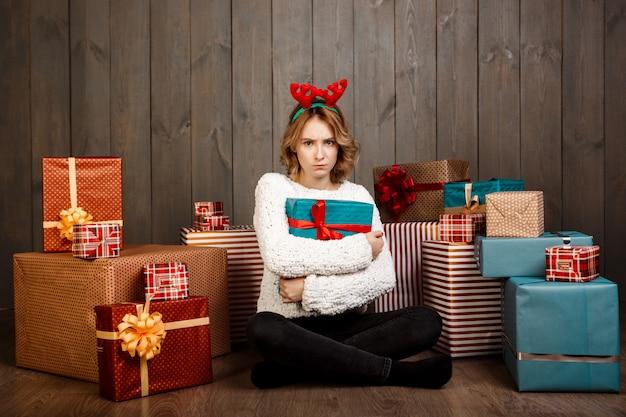 Jonge mooie meisjeszitting onder kerstmisgiften over houten muur
