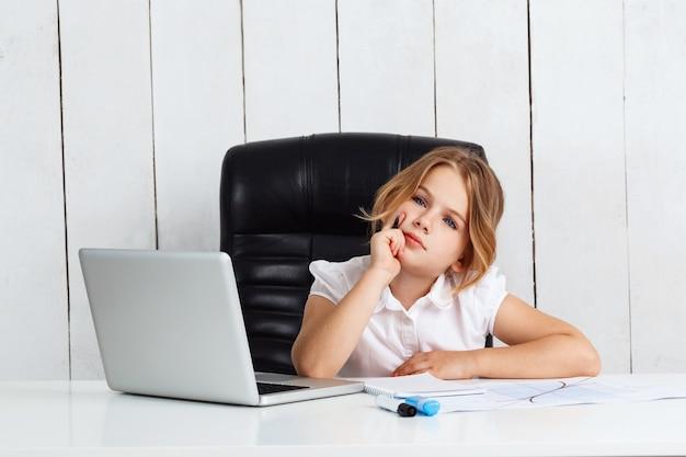 Jonge mooie meisjeszitting op werkende plaats in bureau.
