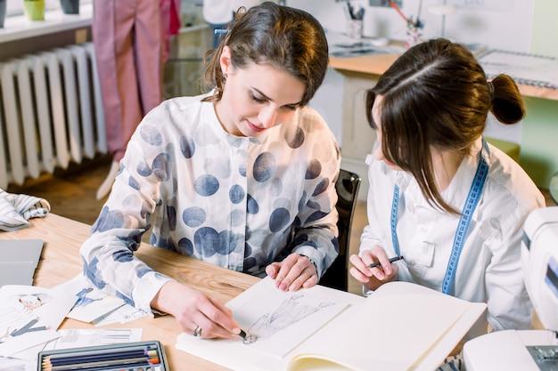 Jonge mooie mode-ontwerper en naaister in mode-atelier tekenen schets van stijlvolle broek. het proces van het ontwerpen van kleding.
