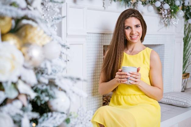 Jonge mooie mode vrouw in gele jurk in de buurt van kerstboom met mok in haar handen mode beau...