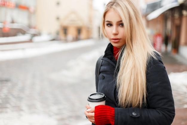 Jonge mooie mode vrouw met koffie in een trendy vintage jas reist in de stad