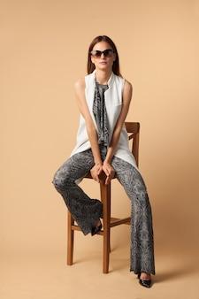 Jonge mooie mode vrouw zittend op een stoel op beige studio achtergrond