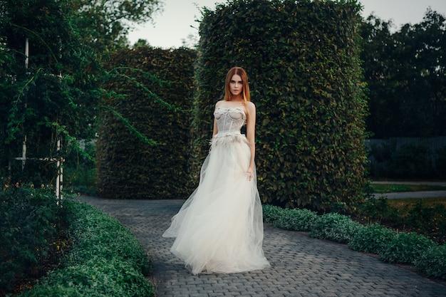 Jonge mooie model is poseren in een lange ivoren jurk in de tuin met een kroon op haar hoofd