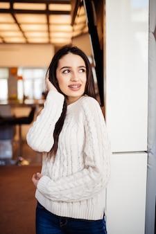 Jonge mooie model met grote ogen rode lippen en lang bruin haar blijven in de kamer bij haar thuis
