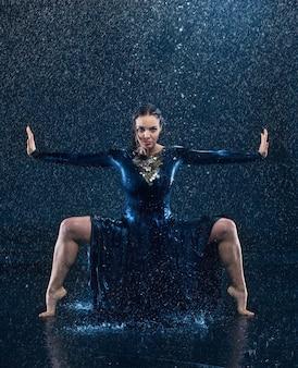 Jonge mooie moderne danser dansen onder waterdruppels