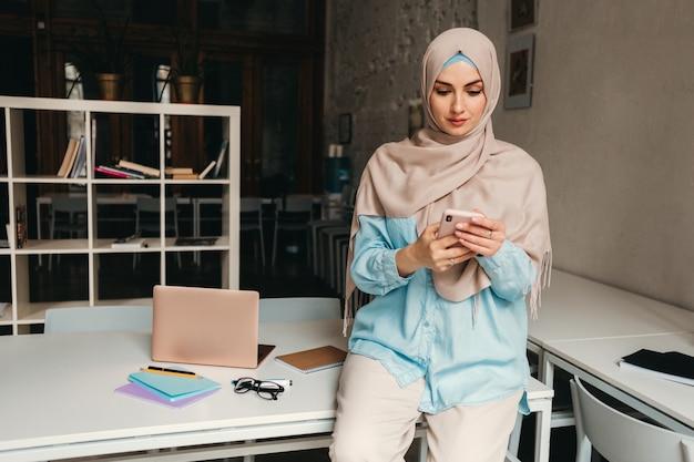 Jonge mooie moderne moslimvrouw in hijab bezig met in kantoorruimte, onderwijs online