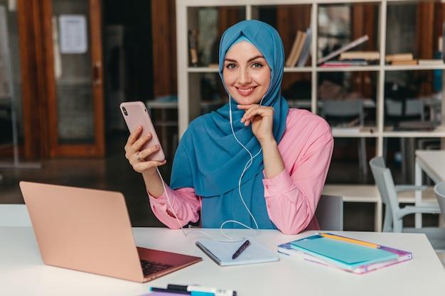 Jonge mooie moderne moslimvrouw in hijab die op laptop in kantoorruimte werkt, online onderwijs education