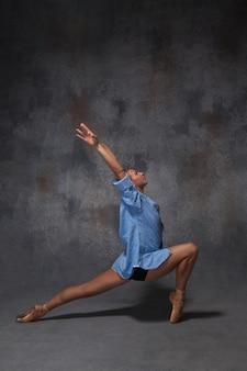 Jonge mooie moderne stijl danseres in een blauw shirt poseren op een grijze achtergrond