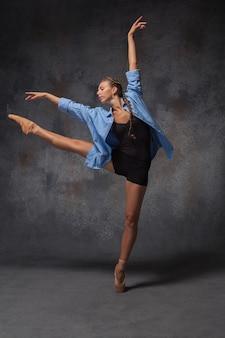 Jonge mooie moderne stijl danseres in een blauw shirt poseren op een studio grijze achtergrond