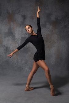 Jonge mooie moderne stijldanser die zich voordeed op een grijze achtergrond