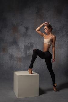 Jonge mooie moderne stijldanser die zich voordeed op witte kubus op grijze achtergrond
