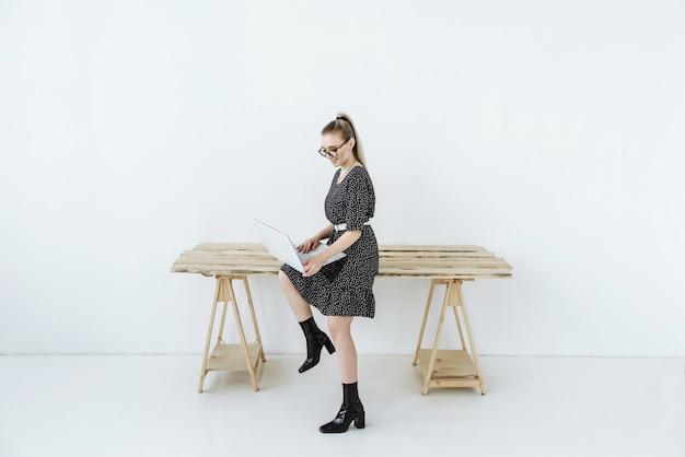 Jonge mooie moderne vrouw in een jurk en bril zit aan tafel en werkt op internet op een laptop