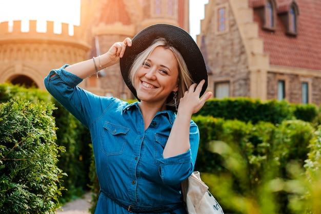 Jonge mooie modieuze gelukkige vrouw tegen de middeleeuwse oude stad