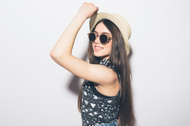 Jonge mooie modieuze vrouw met trendy make-up in zwarte hoed en bril op de grijze muur. model kijken, stijlvolle bril dragen. vrouwelijke mode, beauty concept.