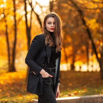 Jonge mooie modieuze vrouw model met rode lippen in een trendy pak met een mode blazer, trui en jeans wandelingen in herfst park met gekleurde herfst oranje gebladerte bij zonsondergang