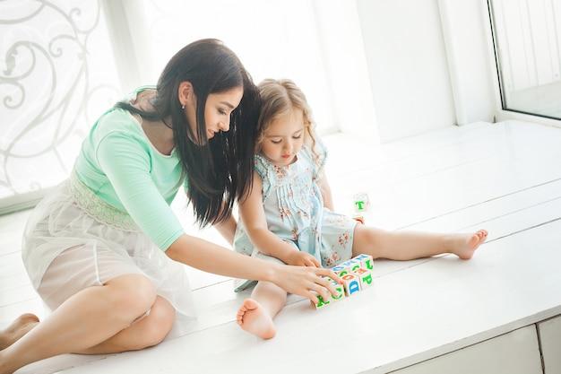 Jonge mooie moeder die alfabet met haar kleine dochter bestudeert