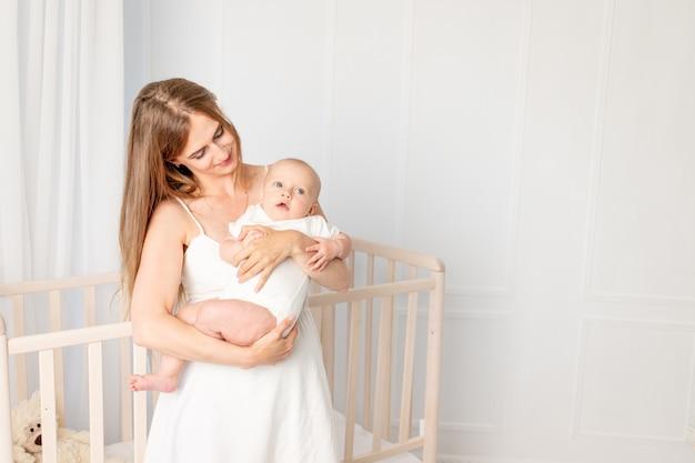Jonge mooie moeder die haar dochter 6 maanden houdt, haar koesterend in het kinderdagverblijf dat zich door de wieg bevindt, moederdag