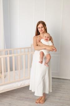 Jonge mooie moeder die haar dochter 6 maanden in de kwekerij houdt die zich door de wieg bevindt, moederdag Premium Foto