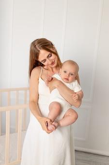 Jonge mooie moeder die haar dochter 6 maanden in de kwekerij houdt, moederdag Premium Foto