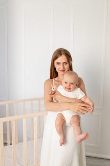 Jonge mooie moeder die haar dochter 6 maanden in het kinderdagverblijf houdt