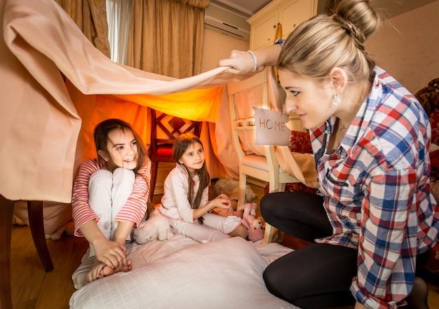 Jonge, mooie moeder die naar twee meisjes kijkt die in de slaapkamer in huis spelen, gemaakt van dekens