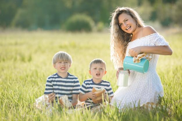 Jonge mooie moeder die picknick met haar kleine kinderen heeft. familie consumptiemelk buitenshuis