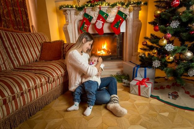 Jonge mooie moeder en baby zittend op de vloer bij open haard versierd voor kerstmis