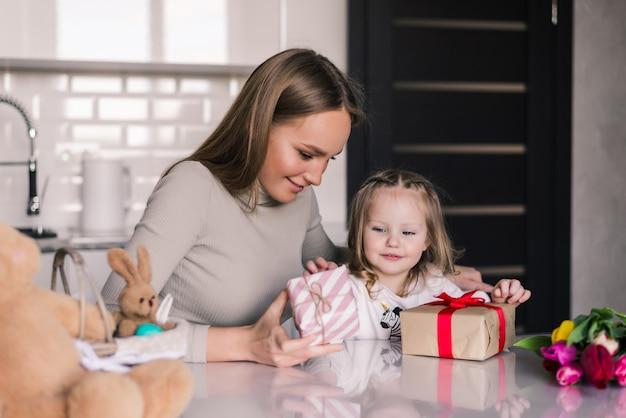 Jonge mooie moeder en dochter met geschenken doos in de keuken