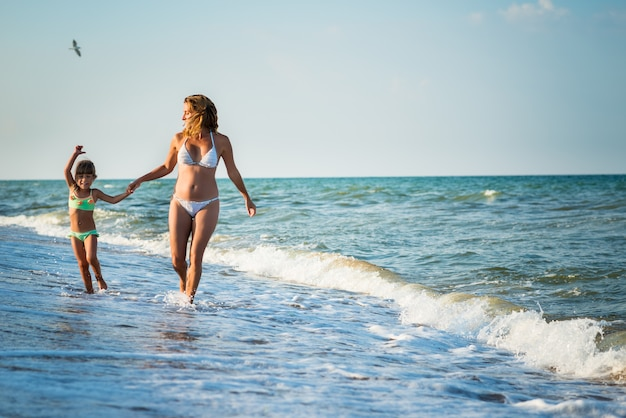 Jonge mooie moeder en dochtertje lopen op de kust tijdens vakantie op een zonnige warme zomerdag tegen een blauwe hemel. concept vakantie met kinderen en wellness