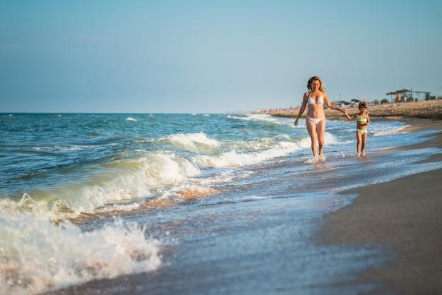 Jonge mooie moeder en dochtertje lopen op de kust tijdens vakantie op een zonnige warme zomerdag tegen een blauwe hemel