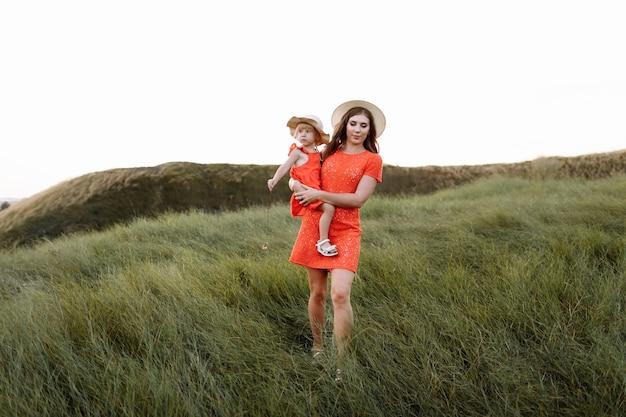 Jonge mooie moeder en dochtertje wandelen op de natuur op zomerdag vakantie