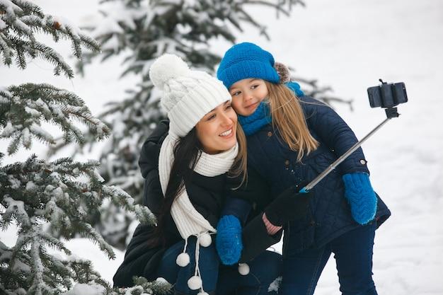 Jonge mooie moeder en haar dochter maken een foto van zichzelf. vrij vrolijke familie selfie maken op de mobiele telefoon