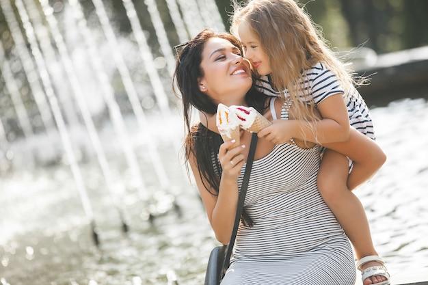 Jonge mooie moeder en haar dochter plezier samen in de buurt van de fontein. mooie vrouw en haar kleine kind eten van ijs. vrolijke familie plezier.