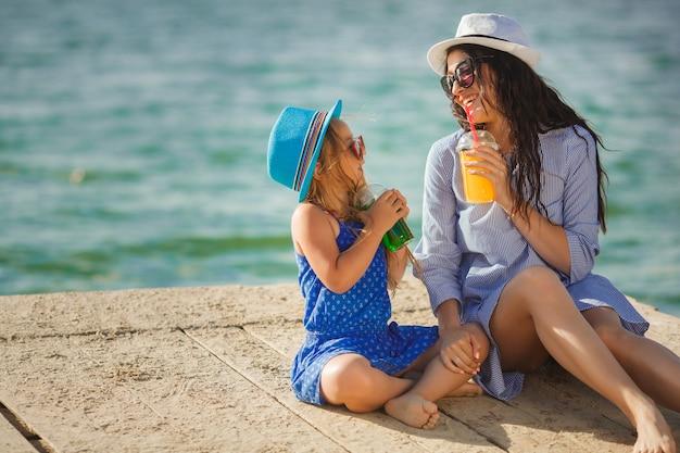 Jonge mooie moeder en haar dochtertje op het strand met plezier. meisjes limonade drinken.