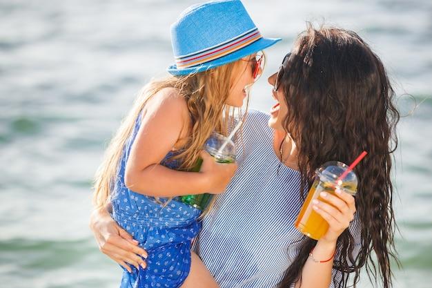 Jonge mooie moeder en haar dochtertje op het strand met plezier