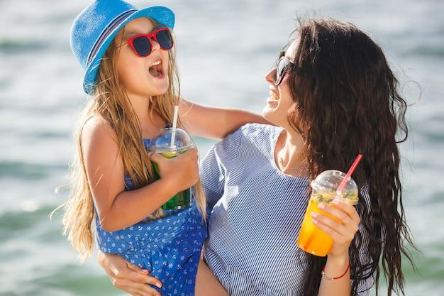 Jonge mooie moeder en haar dochtertje op het strand plezier