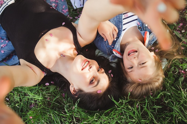 Jonge mooie moeder en haar dochtertje selfie maken op mobiele telefoon. moeder en haar baby meisje buitenshuis plezier in het park. meisjes maken foto op mobiele telefoon en glimlachen